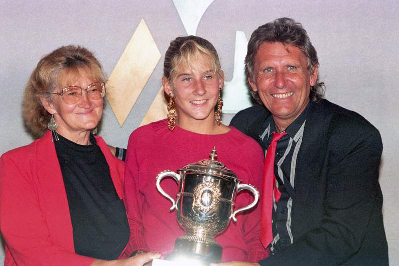 FILE - In this June 10, 1990, file photo, Monica Seles holds her trophy while posing with her parents Esther and Karoli after winning the French Open championship against Steffi Graf at Roland Garros stadium in Paris. (AP Photo/Lionel Cironneau)