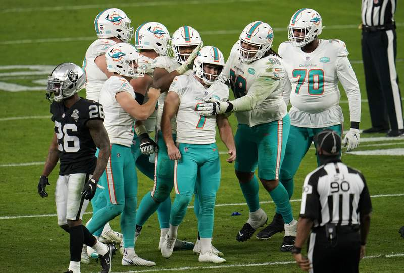 FILE - Miami Dolphins place kicker Jason Sanders (7) celebrates with teammates after kicking the game-winning field goal during the fourth quarter of an NFL football game against the Las Vegas Raiders in Las Vegas, in this Saturday, Dec. 26, 2020, file photo. Dolphins kicker Jason Sanders has signed a $22 million extension through 2026. The deal announced Tuesday, Feb. 16, 2021 includes $10 million guaranteed. (AP Photo/Jeff Bottari, File)