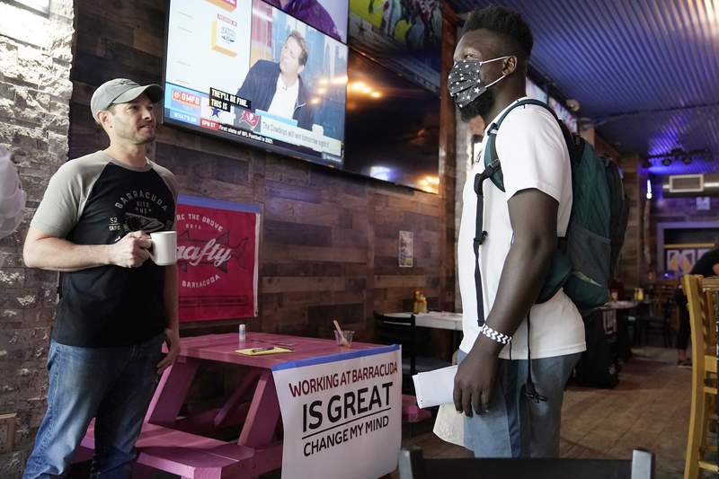 Sudy Gervais, right, talks with Lee Kessler, the owner of the Barracuda Taphouse & Grill, left, about a potential job at a job fair featuring local businesses in the Coconut Grove neighborhood of Miami, Wednesday, Sept. 8, 2021. U.S. economic activity downshifted in July and August due to rising concerns about COVID's delta variant, as well as supply chain problems and labor shortages, the Federal Reserves latest survey of the nation's business conditions revealed.  (AP Photo/Lynne Sladky)