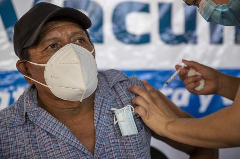 Un trabajador de salud recibe la primera dosis de la vacuna de AstraZeneca contra el COVID-19 el jueves 18 de marzo de 2021 en San Jacinto, en el este de Guatemala. (AP Foto/Moiss Castillo)