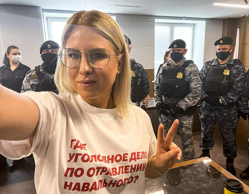 "In this handout photo released by Russian opposition activist Lyubov Sobol in her twitter.com/SobolLubov account, Russian opposition activist Lyubov Sobol wearing in t-short with the words reading ""where is the criminal case for the poisoning of Navalny?"" makes a selfie in front of Russian Federal Bailiffs service officers in a courtroom in Moscow, Russia, on Thursday, April 15, 2021. Sobol, a top associate of Russia's imprisoned opposition leader Alexei Navalny was convicted of trespassing Thursday and handed a suspended sentence of one year community service after she tried to doorstep an alleged security operative believed to be involved in Navalny's poisoning with a Soviet-era nerve agent. (twitter.com/SobolLubov via AP)"
