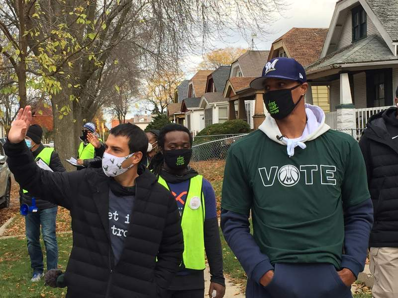 """FILE - In this Oct. 24, 2020 file photo, Milwaukee Bucks senior vice president Alex Lasry, left, and Bucks guard George Hill walk through a Milwaukee neighborhood during a voter canvassing effort. Lasry received the COVID-19 vaccine this week at a senior living center in Milwaukee. Alex Lasry told the Milwaukee Journal Sentinel in a story published Friday, Jan. 29, 2021, that he """"just got lucky"""" and didn't receive any favoritism. (AP Photo/Steve Megargee File)"""