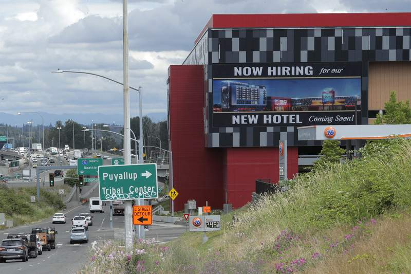 """FILE - In this July 9, 2020, file photo, a large video display reads """"Now hiring for our new hotel coming soon!,"""" at the new Emerald Queen Casino, which is open, and owned by the Puyallup Tribe of Indians, in Tacoma, Wash. The United States added 1.8 million jobs in July, a pullback from the gains of May and June and evidence that the resurgent coronavirus has weakened hiring and the economic rebound. (AP Photo/Ted S. Warren, File)"""