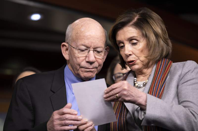 FILE - In this Jan. 29, 2020, file photo, House Speaker Nancy Pelosi of Calif., right, shows a note to Rep. Peter DeFazio, D-Ore., during a news conference on Capitol Hill in Washington. The House has approved a $1.5 trillion plan to rebuild the nations crumbling infrastructure, pouring hundreds of billions of dollars into projects to fix roads and bridges, upgrade transit systems, expand interstate railways and dredge harbors, ports and channels. (AP Photo/ Jacquelyn Martin, File)