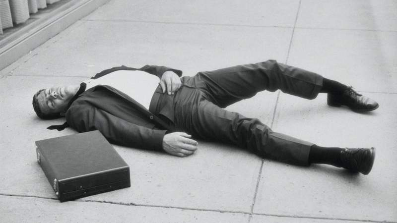 A businessman lying in the streets in the 60s.