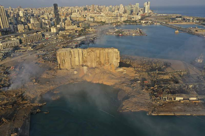FILE - In this Aug 5, 2020 file photo, a drone camera captures the scene of an explosion that hit the seaport of Beirut, Lebanon. The Aug. 4 blast at Beirut's port tore through the city at 6:07 p.m., destroying entire neighbourhoods and killing scores of people. (AP Photo/Hussein Malla, File)