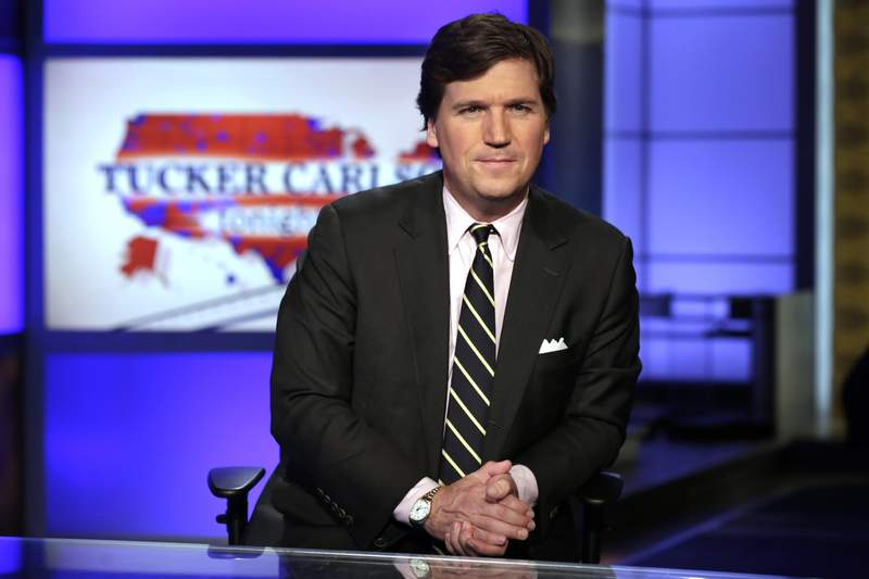 """FILE - In this March 2, 2017 file photo, Tucker Carlson, host of """"Tucker Carlson Tonight,"""" poses for photos in a Fox News Channel studio, in New York. Carlson, who on Monday's show addressed the story of his former top writer, Blake Neff, who resigned after CNN found he had written a series of controversial tweets under a pseudonym, has left for vacation. It fits a pattern at Fox, whose personalities tend to go away to cool off when the heat is on. Carlson's vacation is the sixth example in a little more than three years. A Fox representative confirmed Carlson's vacation was planned before the Neff story broke. (AP Photo/Richard Drew, File)"""