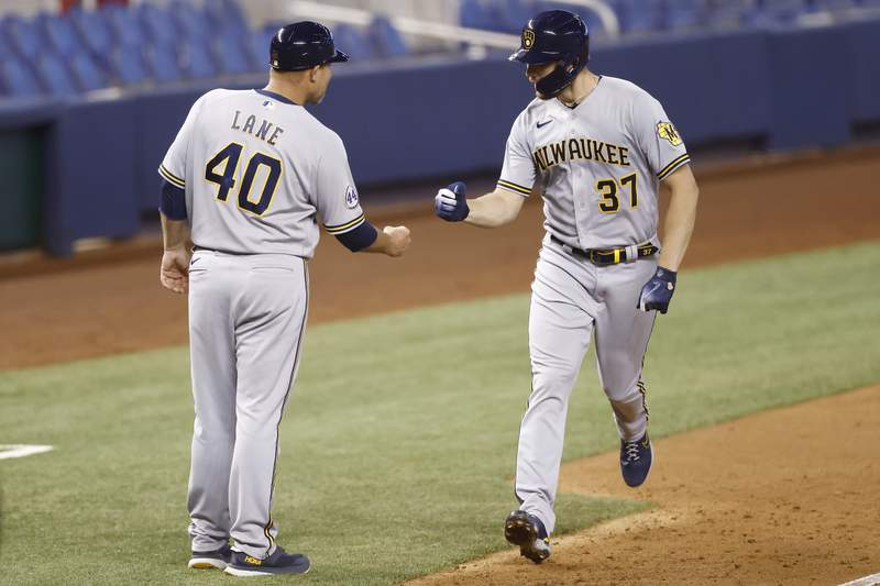 Adrian Houser of the Milwaukee Brewers celebrates with third base coach Jason Lane after hitting a solo home run during the fourth inning against the Miami Marlins at loanDepot park on May 08, 2021 in Miami, Florida.