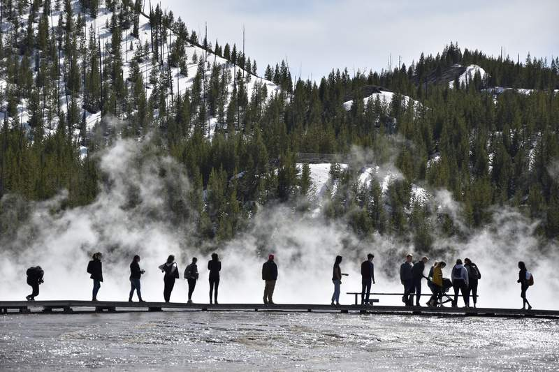 Visitors are seen at Grand Prismatic Spring in Yellowstone National Park, Wyoming on May 1, 2021. A study by federal and university researchers says average park temperatures in recent decades were likely the warmest of the last 800,000 years. (AP Photo/Iris Samuels)