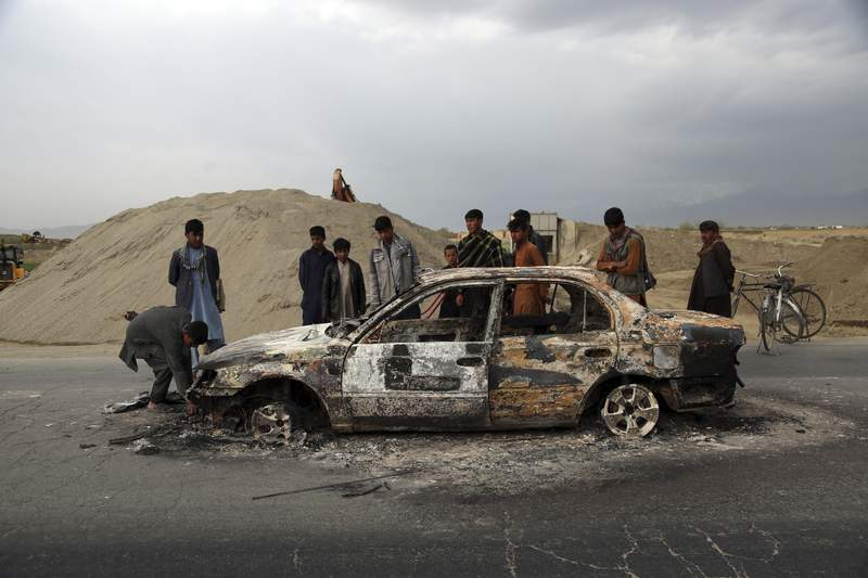 FILE - In this April 9, 2019, file photo, Afghans watch a civilian vehicle burnt after being shot by U.S. forces following an attack near the Bagram Air Base, north of Kabul, Afghanistan. Three American service members and a U.S. contractor were killed when their convoy hit a roadside bomb on Monday near the main U.S. base in Afghanistan, the U.S. forces said. The Taliban claimed responsibility for the attack. Intelligence alleging that Afghan militants might have accepted Russian bounties for killing American troops didnt scuttle the U.S.-Taliban agreement or President Donald Trumps plan to withdraw thousands more troops from the war. (AP Photo/Rahmat Gul, File)