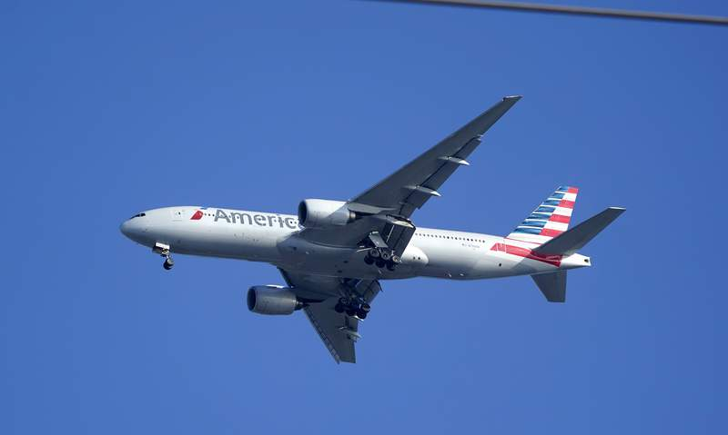 An American Airlines Boeing 777 is framed by utility wires as it prepares to land at Miami International Airport, Wednesday, Jan. 27, 2021, in Miami.   The airline said Thursday that it lost $2.2 billion in the fourth quarter, with revenue plunging by nearly two-thirds from a year earlier. And the airline lost $8.9 billion for the full year after earning nearly $1.7 billion in 2019.  .(AP Photo/Wilfredo Lee)