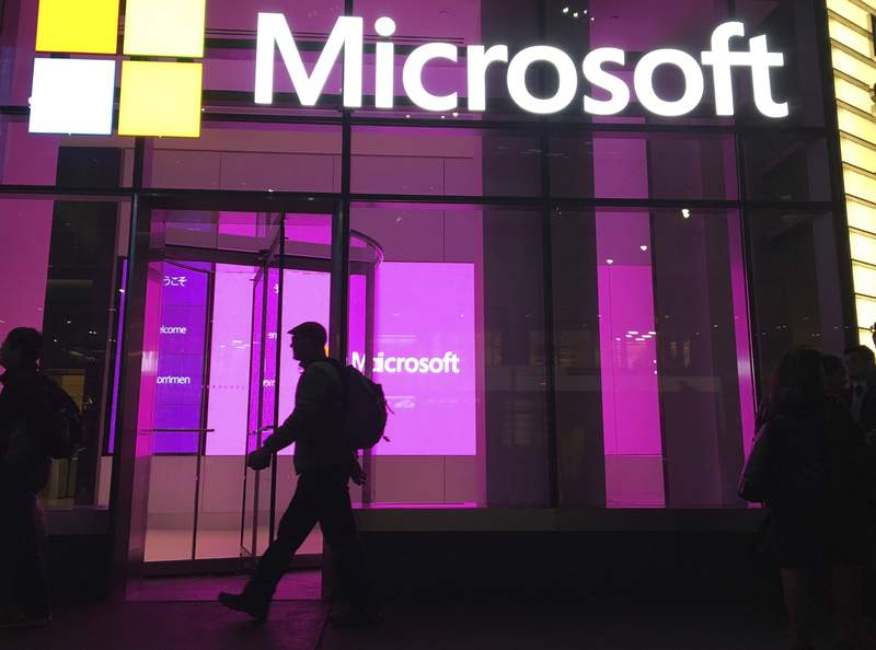FILE - In this Nov. 10, 2016, photo, people walk near a Microsoft office in New York.  Microsoft says Iranian hackers have posed as conference organizers in Germany and Saudi Arabia in an attempt to spy on high-profile people using spoofed email invitations. The tech company said Wednesday, Oct. 28, 2020, it detected attempts by the hacking group it calls Phosphorus to trick former government officials, policy experts and academics.  (AP Photo/Swayne B. Hall)