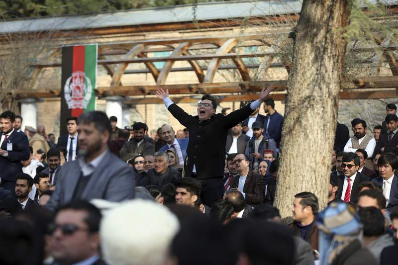 Afghan people chant after a few rockets are fired during inauguration ceremony for Afghan President Ashraf Ghani at the presidential palace in Kabul, Afghanistan, Monday, March 9, 2020. (AP Photo/Rahmat Gul)