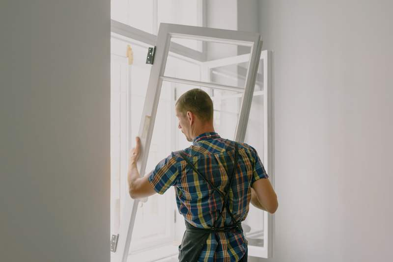 A man removes a window from a pane.