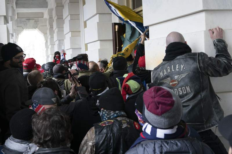 FILE - In this Jan. 6, 2021 file photo insurrectionists loyal to President Donald Trump try to open a door of the U.S. Capitol as they riot in Washington. With riot cases flooding into Washingtons federal court, the Justice Department is under pressure to quickly resolve the least serious cases. (AP Photo/Jose Luis Magana, File)