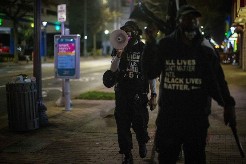 """Aubrey """"Japharii"""" Jones, left, walks on the sidewalk on Atlantic Ave. Saturday March 27, 2021 in Virginia Beach, Va.. Overnight shootings near the Atlantic oceanfront in Virginia Beach left two people dead and eight wounded in a scene described by authorities on Saturday as very chaotic. (AP Photo/John C. Clark)"""