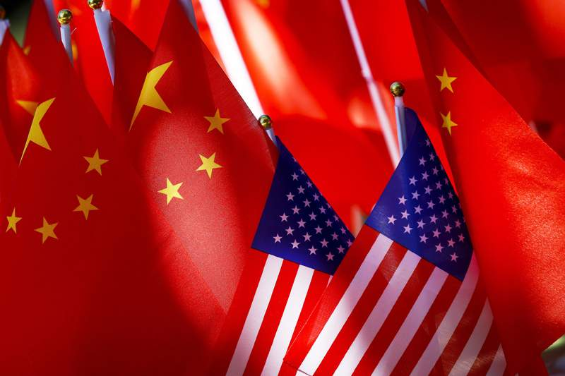 In this Sept. 16, 2018, file photo, American flags are displayed together with Chinese flags on top of a trishaw in Beijing. Under scathing political attacks from the Trump administration, China is defending its Confucius Institutes as apolitical facilitators of cultural and language exchange. he administration last week urged U.S. schools and colleges to rethink their ties to the institutes that bring Chinese language classes to America but, according to federal officials, also invite a malign influence from China. (AP Photo/Andy Wong, File)