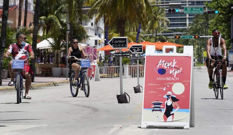 "Bike riders ride past a ""Mask Up Miami Beach,"" sign in Miami Beach. (AP Photo/Wilfredo Lee)"