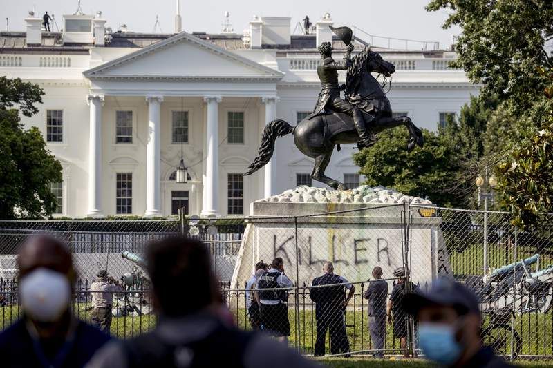 """The White House is visible behind a statue of President Andrew Jackson in Lafayette Park, Tuesday, June 23, 2020, in Washington, with the word """"Killer"""" spray painted on its base. Protesters tried to topple the statue Monday night. President Tump had tweeted late Monday that those who tried to topple the statue of President Andrew Jackson in Lafayette Park across the street from the White House faced 10 years in prison under the Veteran's Memorial Preservation Act.  (AP Photo/Andrew Harnik)"""