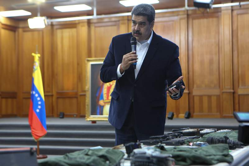 This photo released by the Venezuelan Miraflores presidential press office shows President Nicolas Maduro speaking over military equipment that he says was seized during an incursion into Venezuela, during his televised address from Miraflores in Caracas, Venezuela, Monday, May 4, 2020. Maduro said authorities arrested two U.S. citizens among a group of mercenaries on Monday, a day after a beach raid purportedly aimed at capturing the leader that Venezuelan authorities say they foiled. (Miraflores press office via AP)