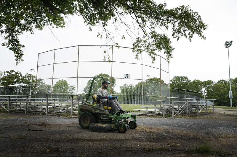 This April 22, 2020 photo, Memphis Little League President Kerry Cobb rides a lawn mover after cutting outfield grass at Will Carruthers Park in Memphis, Tenn. The city had shuttered its baseball program due to coronavirus concerns.  (Mark Weber/Daily Memphian via AP)