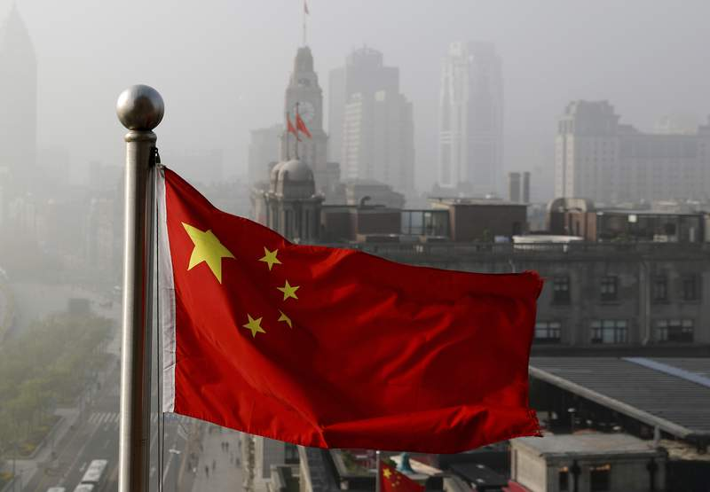 FILE - In this April 14, 2016 file photo, a Chinese national flag flutters against the office buildings in Shanghai, China. Twitter locked Chinas U.S. Embassy account because of a tweet in support of Chinas policies on Muslims and ethnic minorities in the western Xinjiang, The tweet on Jan. 7, 2021 says Uygur women in Xinjiang have been emancipated and are no longer baby making machines. Twitter said it removed the tweet because it violates its policy on dehumanization.  (AP Photo/Andy Wong, File)