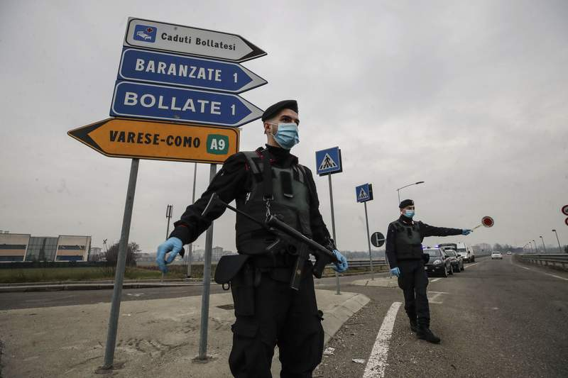 FILE - Carabinieri officers patrol one of the main access road to Bollate, in the outskirts of Milan, Italy. Italys northern Lombardy region, where Europe's coronavirus outbreak erupted last year, asked the national government Thursday to send more vaccines north to help stem a surge of new cases that are taxing the hospital system in the province of Brescia. Brescia, with a population of around 1.2 million, has seen its daily caseload go from the mid-100s at the start of February to 901 on Wednesday thanks in part to clusters of cases traced to the British variant.  (AP Photo/Luca Bruno)