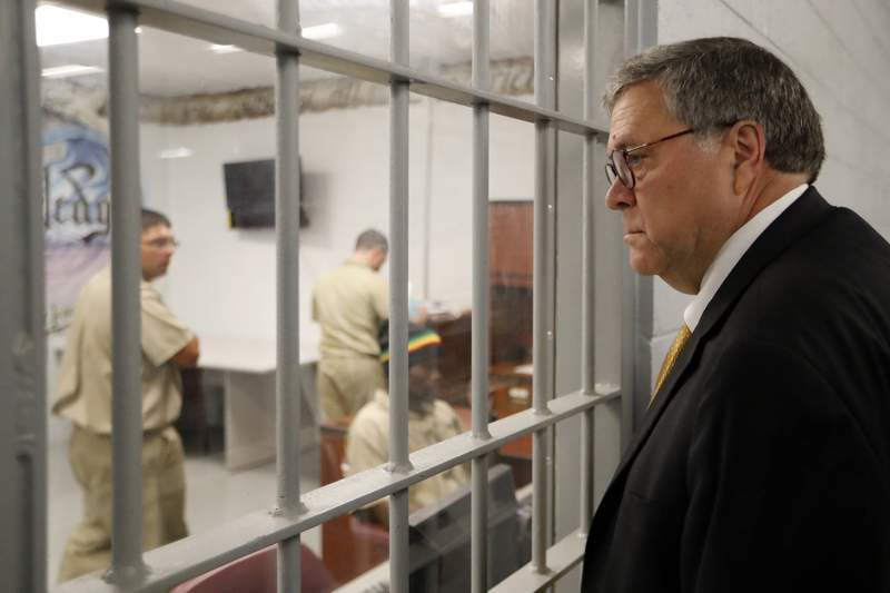 FILE - In this July 8, 2019, file photo, Attorney General William Barr watches as inmates work in a computer class during a tour of a federal prison. in Edgefield, S.C. The Justice Department is making changes to its system used to identify whether an inmate is likely to commit crimes again after release from prison to ensure the process is fair and effective. It's part of a sweeping criminal justice overhaul measure that was enacted last year. The federal Bureau of Prisons has already assessed nearly all of the 175,269 inmates in federal custody. But the Justice Department plans to re-screen all of those inmates under new guidelines, which officials say places a stronger emphasis on accurately measuring an inmates change behind bars. (AP Photo/John Bazemore, File)