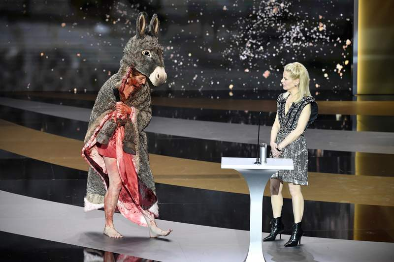 """rench actress Corinne Masiero (L) delivers a speech wearing a """"Peau d'Ane"""" costume next to French actress and Master of Ceremony Marina Fois during the 46th Cesar Award ceremony on Friday, March 12, 2021 in Paris. (Bertrand Guay, Pool via AP)"""
