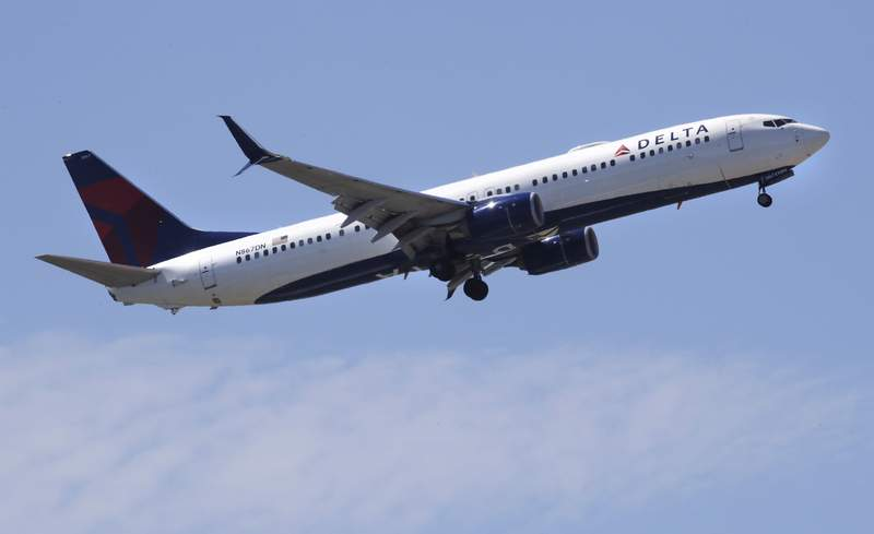 FILE- In this May 24, 2018, file photo a Delta Air Lines passenger jet plane, a Boeing 737-900 model, approaches Logan Airport in Boston.  Airlines are seeing a sharp drop in bookings and a rise in cancellations in recent days as the coronavirus outbreak continues to spread, and they are responding by slashing flights and freezing hiring.   Normally airlines try to lure reluctant customers by discounting fares, but that won't work in the face of the COVID-19 outbreak. (AP Photo/Charles Krupa, File)