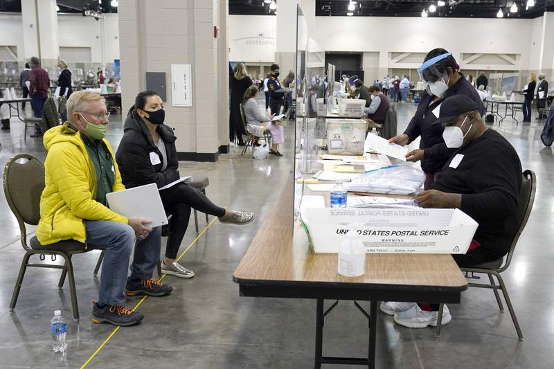 FILE - Election workers, right, verify ballots as recount observers, left, watch during a Milwaukee hand recount of presidential votes at the Wisconsin Center, Friday, Nov. 20, 2020, in Milwaukee. Wisconsin finished a partial recount of its presidential results on Sunday, Nov. 29, 2020 confirming Democrat Joe Biden's victory over President Donald Trump in the key battleground state. Trump vowed to challenge the outcome in court. (AP Photo/Nam Y. Huh)