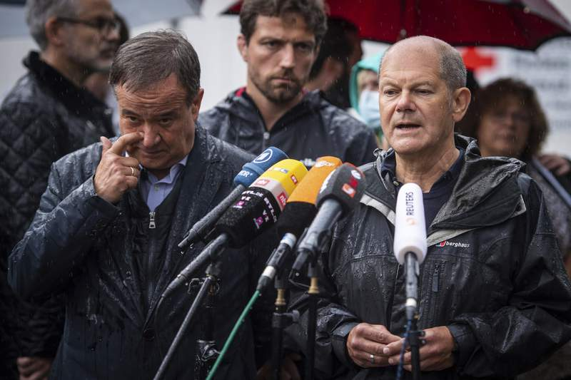 FILE - In this Tuesday, Aug.3, 2021 file photo Armin Laschet, top canditate of the German Christian Democrats for the federal elections, and Olaf Scholz, top canditate of the German Social Democrats, address the media during a press conference in Stolberg, Germany that was hit by heavy rain and floods. Climate change is among the top concerns for Germans going into this year's national election that will determine who replaces Angela Merkel as Chancellor. But while voters admit they are worried about the state of the planet, especially after last the deadly floods that hit Germany in July, many fear the cost of backing the environmentalist Green party that's campaigned strongest for meeting the Paris climate accord's goals.  (Marius Becker/DPA via AP, Pool, file)