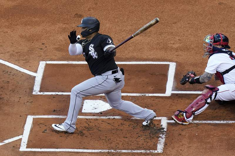 FILE - In this April 18, 2021, file photo, Chicago White Sox's Yermin Mercedes swings at a pitch next to Boston Red Sox's Christian Vazquez during a baseball game in Boston. Mercedes, the surprising rookie who helped carry the White Sox with his booming bat early in the season and got sent to the minors following a prolonged slump, says he is stepping away from baseball. Mercedes announced his decision on Instagram on Wednesday, July 21. (AP Photo/Steven Senne, File)