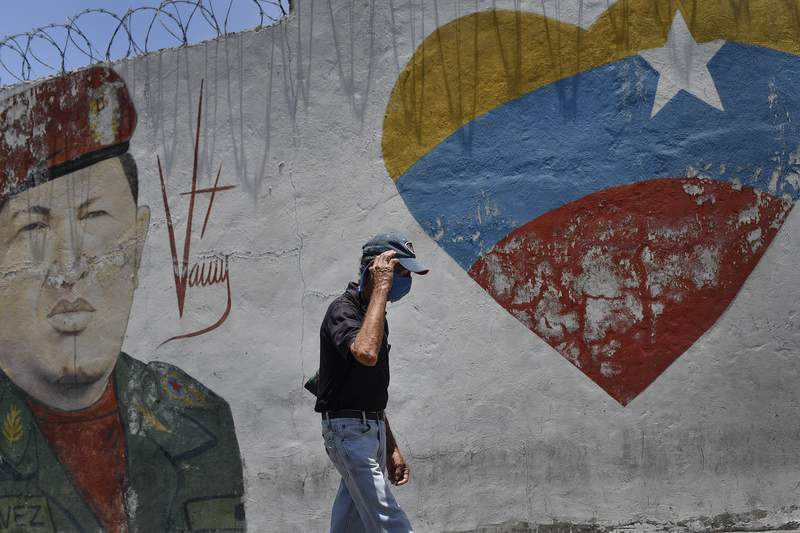 A man, wearing a protective face mask as a precaution against the new coronavirus, walks past a mural of the late Venezuelan President Hugo Chavez in the 23 de Enero neighborhood of Caracas, Venezuela, Saturday, April 11, 2020. (AP Photo/Matias Delacroix)