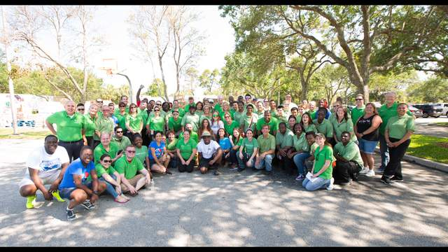 Publix employees pose for a photograph with CEO Ed Crenshaw during the grocery store chain's annual service day event.