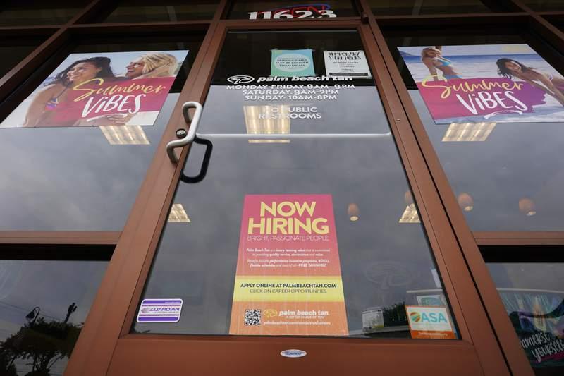 Un letrero de contrataciones abiertas (abajo) se observa en un negocio de bronceado en Richmond, Virginia, el mircoles 2 de junio de 2021. (AP Foto/Steve Helber)