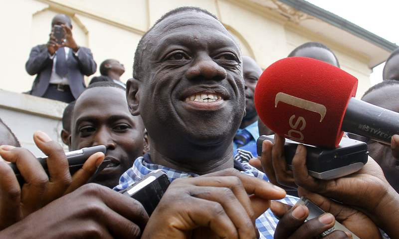 FILE - In this Tuesday, July 12, 2016 file photo, former presidential candidate Kizza Besigye, center, is interviewed by journalists after being released on bail after spending two months in jail over treason charges at the High Court in Kampala, Uganda. The longtime opposition leader in Uganda announced on Wednesday, Aug. 19, 2020 that he will not run against President Yoweri Museveni in polls scheduled for 2021, saying he will continue seeking democratic change by other means. (AP Photo/Stephen Wandera, File)