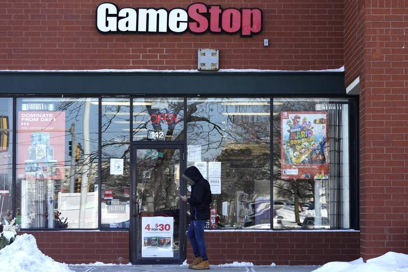 FILE - In this Jan. 28, 2021 file photo, a customer checks on his cellphone as he walks to a GameStop store in Vernon Hills, Ill. The frenzy around GameStops stock may have quieted down, but the outsized influence small investors had in the saga is likely to stick around. While no one expects another supernova like GameStop, the tools that smaller investors employed to supercharge its stock can be used again and again.  (AP Photo/Nam Y. Huh, File)