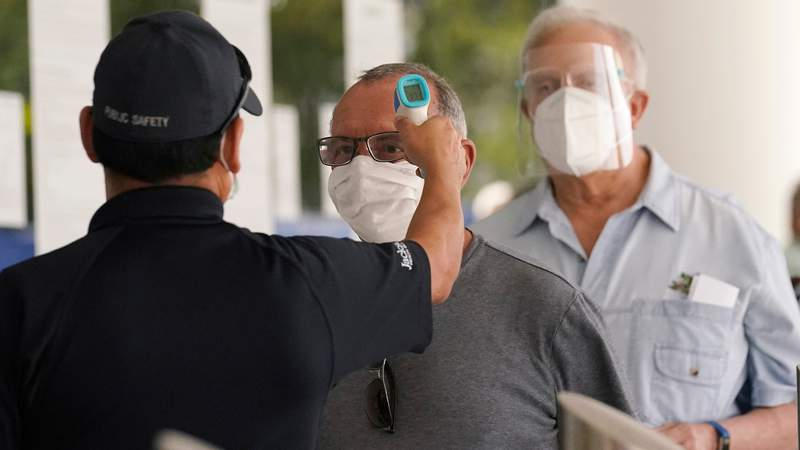 Floridians have their temperatures taken before receiving the second dose of the Pfizer COVID-19 vaccine at Jackson Health System in Miami.