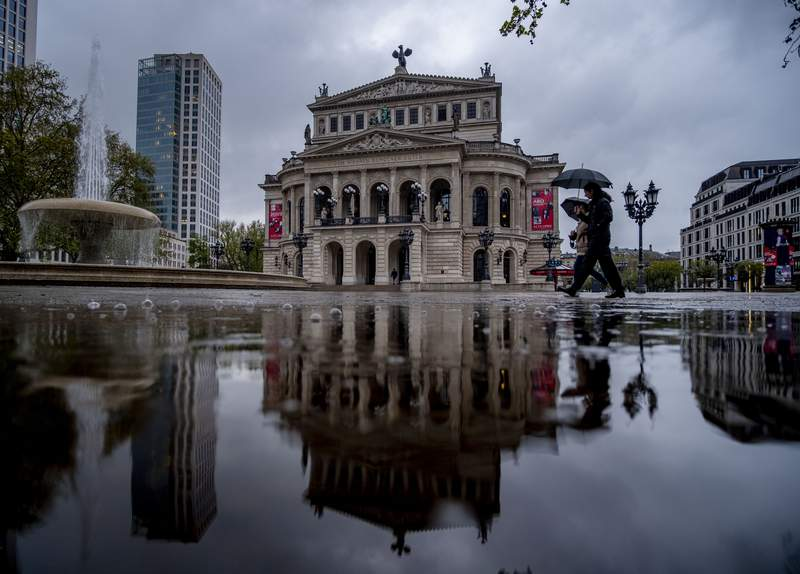 The Old Opera house is reflected in a puddle in Frankfurt, Germany, on a rainy Thursday, May 6, 2021. (AP Photo/Michael Probst)