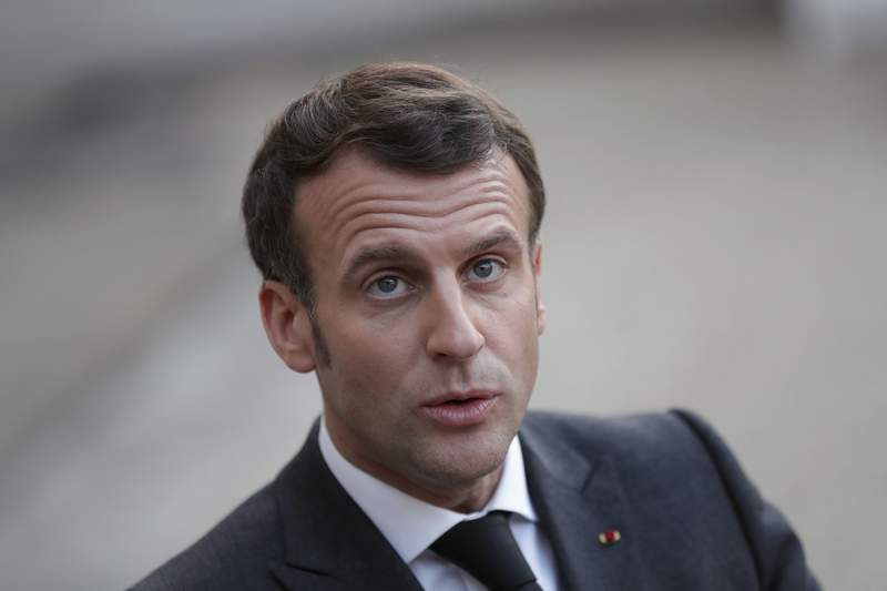 French President Emmanuel Macron arrives to deliver a speech at the end of a meeting with Mohammad Younes Menfi, president of Libya's Presidential Council and Musa al-Koni, vice-president of Libya's Presidential Council, at the Elysee Palace, in Paris, Tuesday, March 23, 2021. Macron said France will reopen its embassy in Libya's capital Tripoli on Monday as a gesture of support for the new interim government. (AP Photo/Thibault Camus)