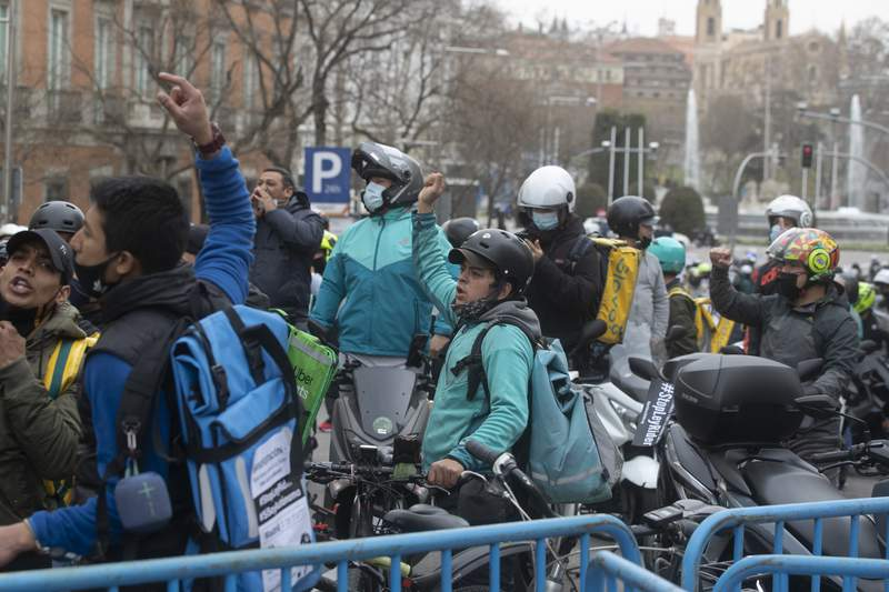 """Delivery riders protest outside the Spanish parliament in Madrid, Wednesday March 3, 2021.The Spanish government announced on Thursday March 11, 2021, legislation that classifies food delivery riders as employees of the digital platforms they work for, not self-employed. Labor Minister Yolanda Daz said Thursday the law is part of """"a modernization of the labor market"""" in Spain, updating regulations in accordance with technological developments to ensure workers' rights are upheld.(AP Photo/Paul White)"""