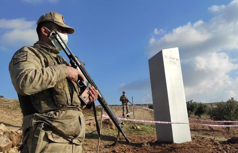 """Turkish police officers guard a monolith, found on an open field near Sanliurfa, southeastern Turkey, Sunday, Feb. 7, 2021. The metal block was found by a farmer Friday in Sanliurfa province with old Turkic script that reads """"Look at the sky, see the moon."""" The monolith, 3 meters high (about 10 feet), was discovered near UNESCO World Heritage site Gobeklitepe with its megalithic structures dating back to 10th millennium B.C. Turkish media reported Sunday that gendarmes were looking through CCTV footage and investigating vehicles that may have transported the monolith. Other mysterious monoliths have popped up and some have disappeared in numerous countries since 2020. (Bekir Seyhanli/IHA via AP)"""