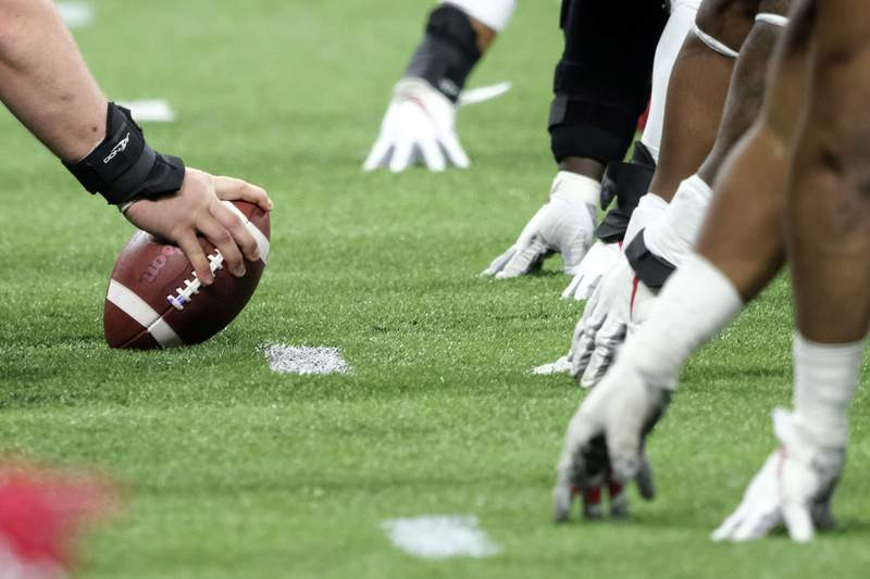 FILE - In this Dec. 7, 2019, file photo, a player prepares to hike the ball at the line of scrimmage during the first half of the Big Ten championship NCAA college football game between Ohio State and Wisconsin in Indianapolis. Don Yee, one of sports' most influential agents, Tom Brady is one of his clients, has teamed with former ESPN and NFL Network executive  Jamie Hemann to develop HUB Football. The concept is simple, though the implementation could be very complex: It will provide opportunities for college players and street free agents to be seen in action by NFL teams.   (AP Photo/AJ Mast, File)