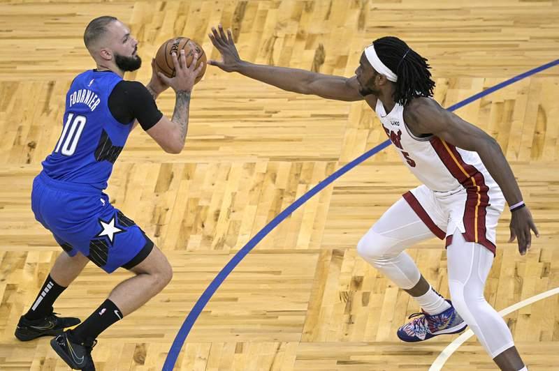 Orlando Magic guard Evan Fournier (10) sets up for a shot in front of Miami Heat forward Precious Achiuwa (5) during the second half of an NBA basketball game Wednesday, Dec. 23, 2020, in Orlando, Fla. (AP Photo/Phelan M. Ebenhack)
