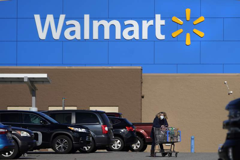 FILE - In this Nov. 18, 2020 file photo, a woman, wearing a protective face mask due to the COVID-19 virus outbreak, wheels a cart with her purchases out of a Walmart store, in Derry, N.H. Walmart, the worlds largest retailer, said Friday, May 14, 2021 that it wont require vaccinated shoppers or workers to wear a mask in its U.S. stores, unless state or local laws say otherwise. Vaccinated shoppers can go maskless immediately, the company said. Vaccinated workers can stop wearing them on May 18. (AP Photo/Charles Krupa, File)
