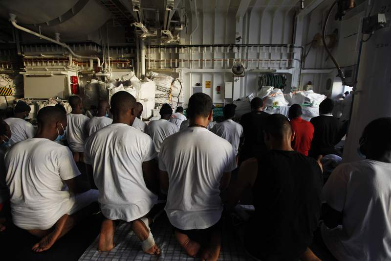 Migrants pray on the deck of the Geo Barents, a rescue vessel operated by MSF (Doctors Without Borders) off Libya, in the central Mediterranean route, Wednesday, Sept. 22, 2021. (AP Photo/Ahmed Hatem)