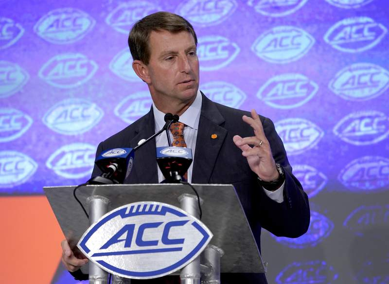FILE - Clemson head coach Dabo Swinney speaks during the Atlantic Coast Conference NCAA college football media day in Charlotte, N.C., in this Wednesday, July 17, 2019, file photo. The post-Trevor Lawrence era begins at Clemson with the Tigers still the prohibitive favorites to win the Atlantic Coast Conference for a seventh straight season. On the latest AP Top 25 Podcast, David Hale from ESPN joins APs Ralph Russo to preview the ACC from Clemson at the top to Syracuse at the bottom.(AP Photo/Chuck Burton, File)