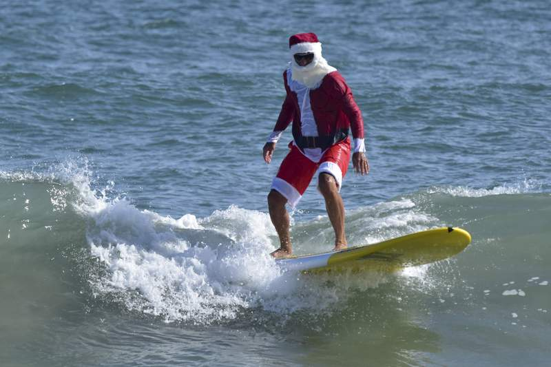 In this handout photo from the Florida Surf Museum on Florida's Space Coast shows a man dressed in a Santa Claus costume surfing Wednesday, Dec. 23, 2020, in Cocoa Beach, Fla. (Florida Surf Museum on Florida's Space Coast via AP)