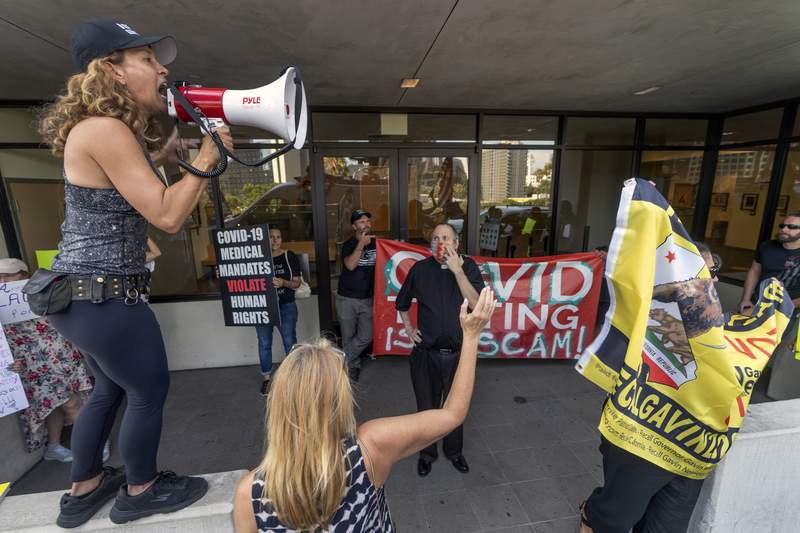 Anti-vaccine mandate protesters and supporters of the California recall election rally outside the front doors of the Los Angeles Unified School District, LAUSD headquarters in Los Angeles Thursday Sept. 9, 2021. The Los Angeles board of education voted Thursday to require students 12 and older to be vaccinated against the coronavirus to attend in-person classes in the nation's second-largest school district. (AP Photo/Damian Dovarganes)